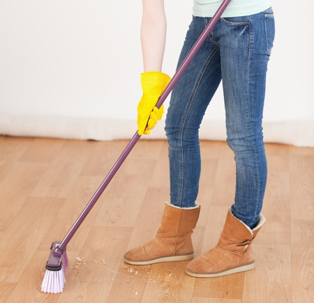 Attractive red-haired woman sweeping the floor at home photo