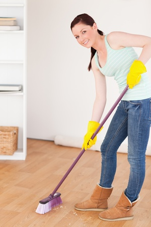 sweep: Good looking red-haired woman sweeping the floor at home