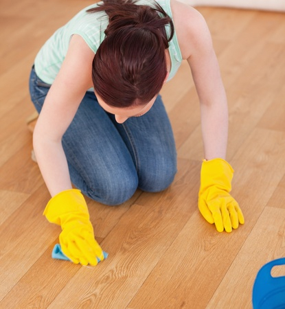 Attractive red-haired woman cleaning the floor while kneeling at home photo