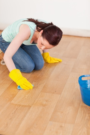 Pretty red-haired woman cleaning the floor while kneeling at home photo