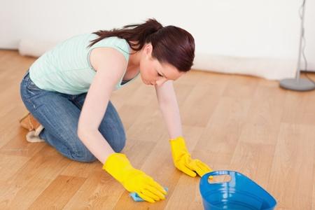 pulizia pavimenti: Bellissima donna dai capelli rossi pulire il pavimento in ginocchio a casa Archivio Fotografico