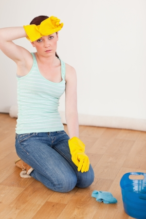 having a break: Good looking red-haired woman having a break while cleaning the floor at home Stock Photo