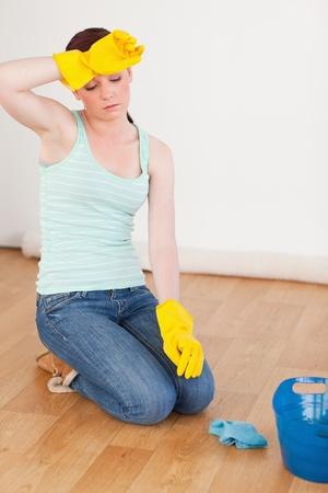 frau sitzt am boden: Attraktive Rothaarige Frau, die eine Pause beim Reinigen des Bodens zu Hause