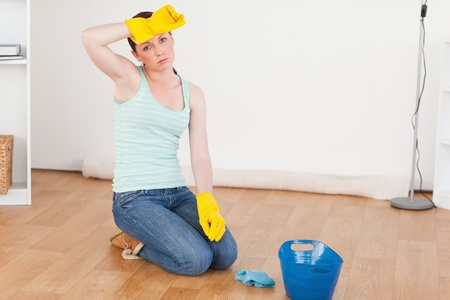 housewife gloves: Cute red-haired woman having a break while cleaning the floor at home