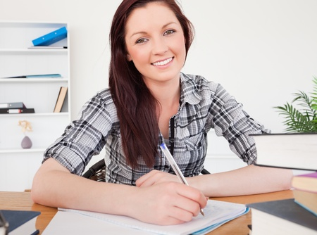 Pretty red-haired female studying at her desk photo