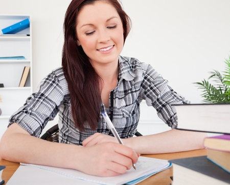 Lovely red-haired female studying at her desk photo