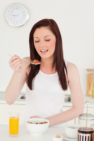 Young beautiful red-haired woman having her breakfast in the kitchen in her appartment  photo