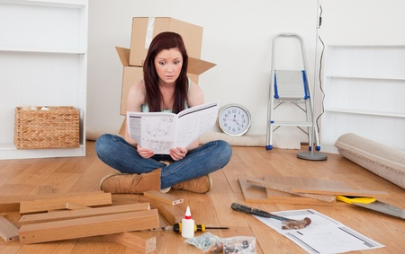 Beautiful red-haired female reading a manual before do-it-yourself at home Stock Photo - 10205281