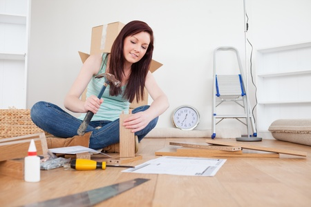 doityourself: Attractive red-haired female nailing a plank at home Stock Photo