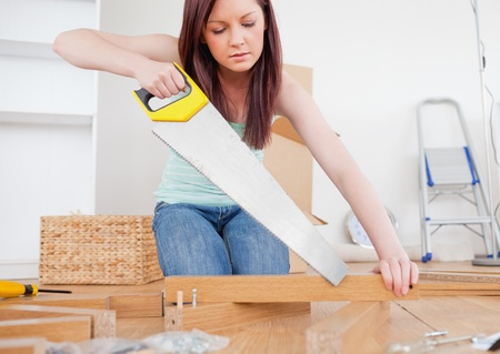 Beautiful red-haired female using a saw for diy at home Stock Photo - 10198731
