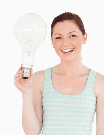 Gorgeous red-haired female holding a light bulb while standing on a white background photo