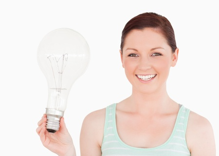 Attractive red-haired female holding a bulb while standing on a white background photo