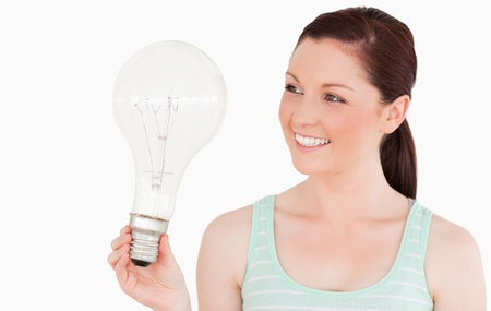 Attractive red-haired female holding a light bulb while standing on a white background Stock Photo - 10192978