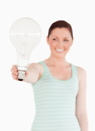 Pretty red-haired female holding a bulb while standing on a white background photo