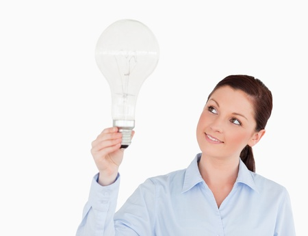 Gorgeous red-haired woman holding a light bulb while standing on a white background photo