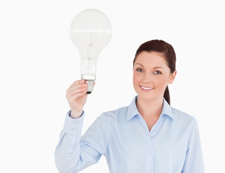 Attractive red-haired woman holding a bulb while standing on a white background photo