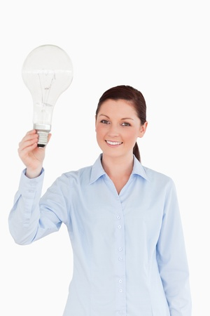 Good looking red-haired female holding a bulb while standing on a white background photo