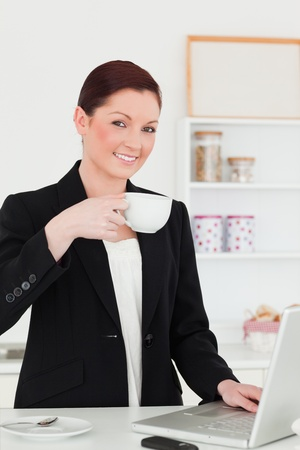 Beautiful red-haired woman in suit relaxing with her laptop while having her breakfast in the kitchen in her appartment photo