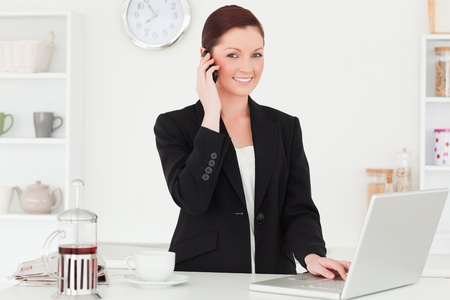 Good looking red-haired woman in suit relaxing with her laptop while phoning in the kitchen in her appartment photo
