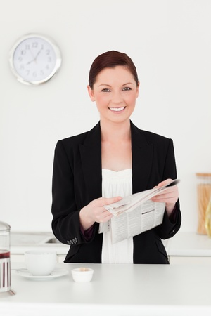 Attractive red-haired woman in suit reading the newspaper in the kitchen in her appartment photo