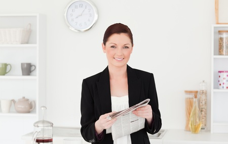 Good looking red-haired woman in suit reading the newspaper in the kitchen in her appartment Stock Photo - 10195643
