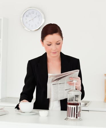 Pretty red-haired woman in suit reading the newspaper in the kitchen in her appartment photo