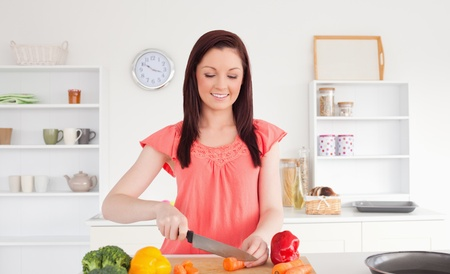 Attractive red-haired woman cutting some vegetables in the kitchen in her appartment photo