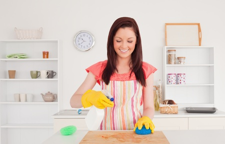 Pretty red-haired woman cleaning a cutting board in the kitchen in her appartment photo
