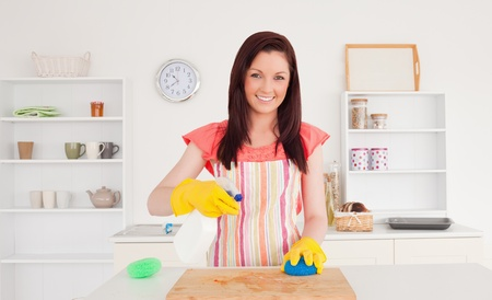 Gorgeous red-haired woman cleaning a cutting board in the kitchen in her appartment photo