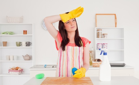 Pretty red-haired woman posing while cleaning a cutting board in the kitchen in her appartment photo