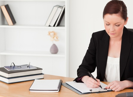 Attractive red-haired woman in suit writing on a notepad while sitting in an office photo