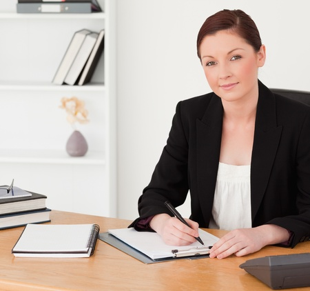 Good looking red-haired woman in suit writing on a notepad while sitting in an office photo