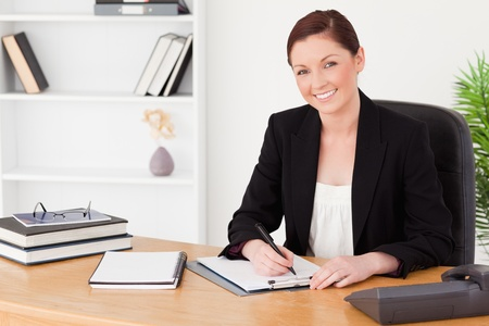 Pretty red-haired woman in suit writing on a notepad while sitting in an office Stock Photo - 10198945