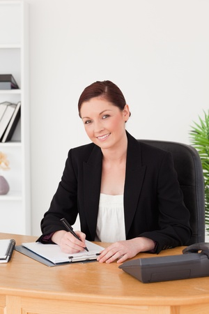 Beautiful red-haired woman in suit writing on a notepad and posing while sitting in an office photo