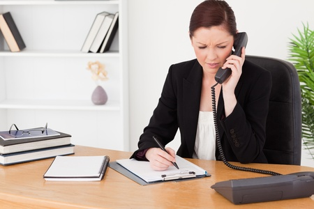 Attractive red-haired woman in suit writing on a notepad and phoning while sitting in an office photo