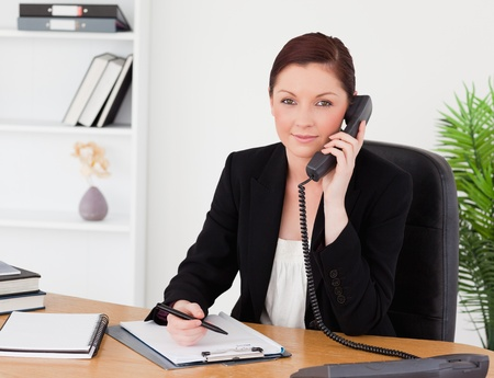Young beautiful red-haired woman in suit writing on a notepad and phoning while sitting in an office photo