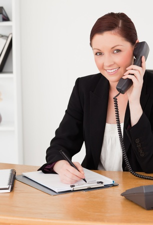Young good looking red-haired woman in suit writing on a notepad and phoning while sitting in an office photo