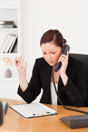 Infuriated beautiful red-haired woman in suit phoning while sitting in an office photo