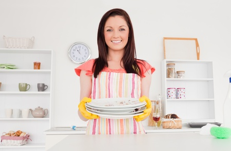 Beautiful red-haired woman posing while holding some dirty plates in the kitchen in her appartment photo