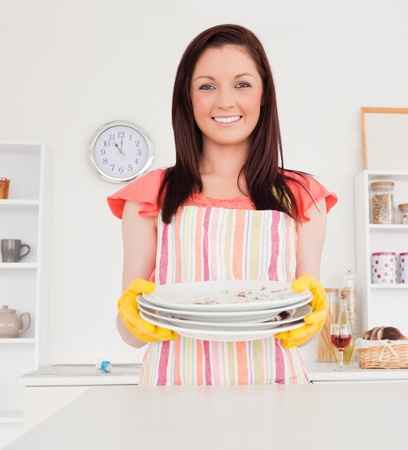 Good looking red-haired woman posing while holding some dirty plates in the kitchen in her appartment photo