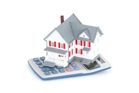 Miniature house with a calculator against a white background photo