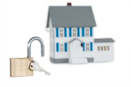 Miniature house and opened padlock against a white background  photo