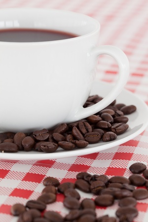 Coffee, saucer and beans on a tablecloth photo