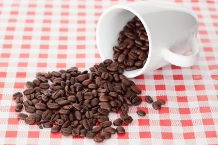 Spilled cup of coffee beans on a table cloth Stock Photo - 10206513