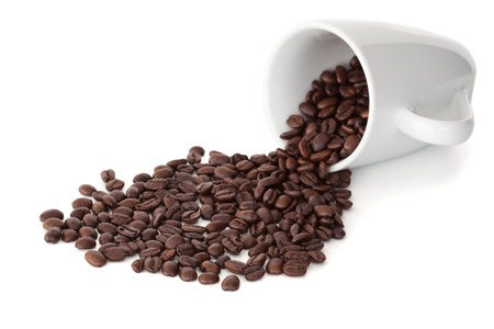 Spilled cup of coffee beans against a white background photo