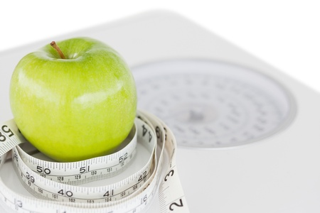 circled: Closeup of a green apple circled with a tape measure and weigh-scale against a white background
