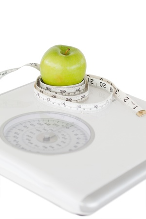 Green apple circled with a tape measure and a weigh-scale against a white background photo