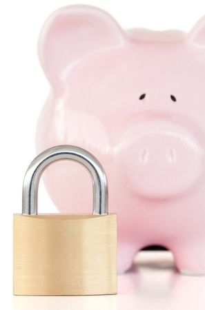 Close up of a pink piggy bank and padlock against a white background.  photo