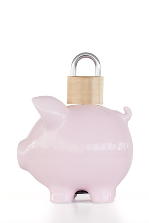 Side view of pink piggy bank and padlock against a white background.  photo