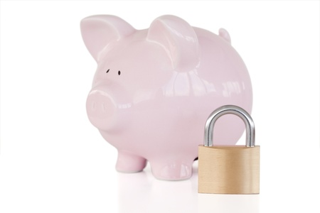 Pink piggy bank and padlock against a white background.  photo
